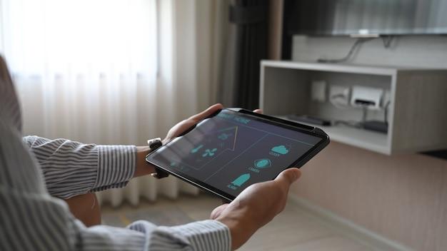 Le mani con immagini ritagliate utilizzano un tablet con applicazioni controllate dai dispositivi domestici sullo schermo. Foto Premium