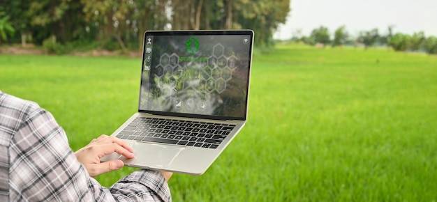 Immagine potata di giovane agricoltore astuto che tiene un computer portatile del computer con l'icona visiva sullo schermo sopra il giacimento del riso come fondo. concetto di tecnologia agricola. Foto Premium