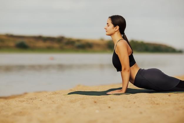 Foto ritagliata della ragazza che pratica yoga, posa del cobra sulla sabbia. Foto Premium