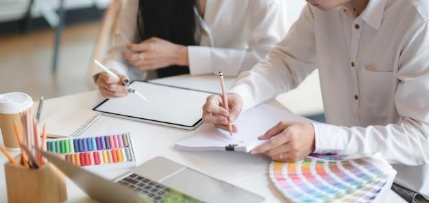 Colpo ritagliato di giovane designer professionista che lavora sui loro concetti insieme al tablet mock-up Foto Premium