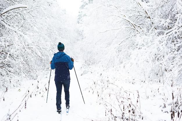 Sci di fondo nella foresta invernale, sciatore in cappello con pompon con bastoncini da sci Foto Premium