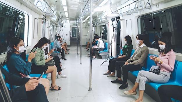 Folla di persone che indossano la maschera per il viso su un viaggio in treno della metropolitana pubblico affollato. malattia da coronavirus o epidemia di pandemia covid 19 e problema dello stile di vita urbano nell'ora di punta. Foto Premium