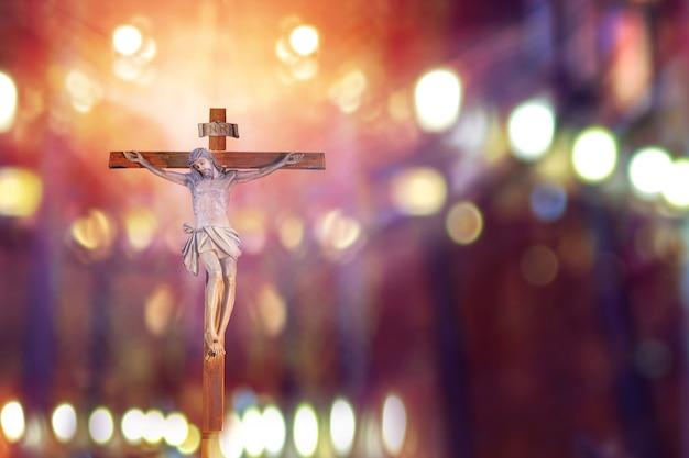 Crocifisso, gesù in croce nella chiesa con raggio di luce dal vetro colorato, festa di pasqua della chiesa cristiana Foto Premium