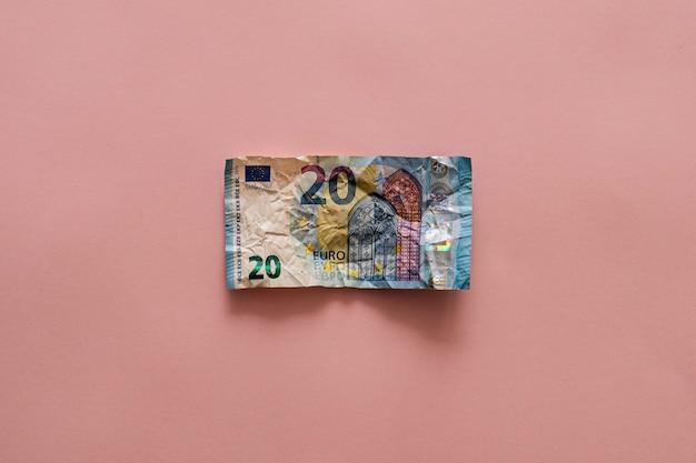 Banconota da 20 euro sgualcita su un tavolo rosa. concetto di risparmio di denaro Foto Premium