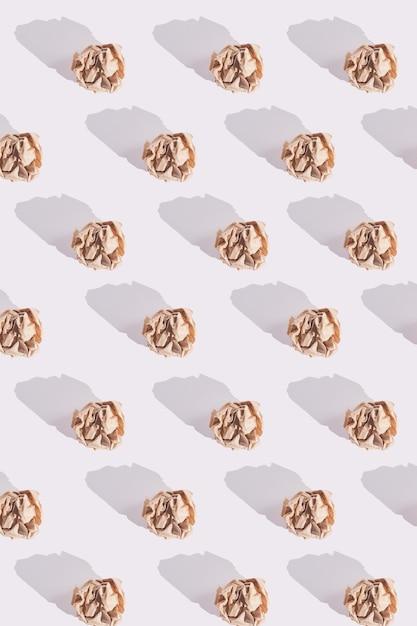 Modello di palline di carta artigianale marrone sgualcito con ombre dure sul bianco Foto Premium