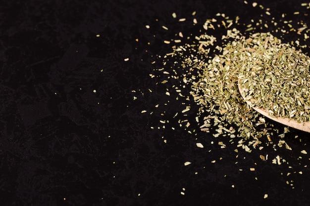 Origano schiacciato sparso in un cucchiaio di legno su una tavola nera. , copyspace. Foto Premium