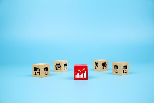 Blog di giocattoli in legno cubo con icona del negozio di marketing in franchising e icona del grafico per la crescita del business. Foto Premium