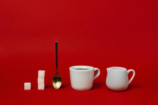 Tazza di americano, cucchiaio d'oro, crema e tazze di zucchero sul rosso Foto Premium