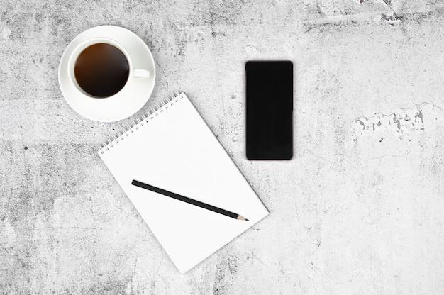 Tazza di caffè sul posto di lavoro. stile piatto laico. spazio di cemento grigio chiaro. Foto Premium