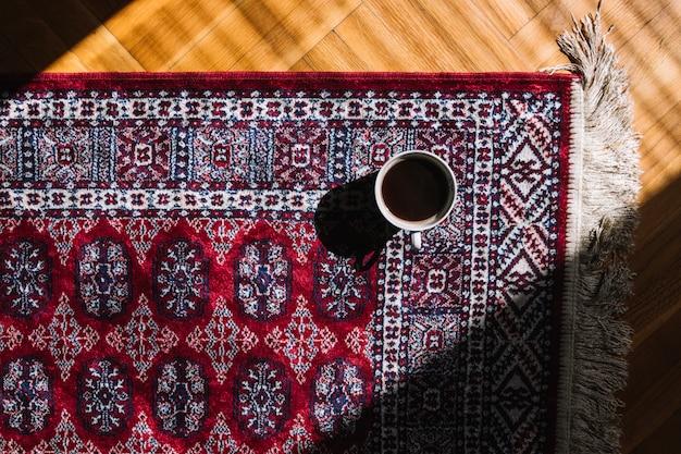 Tazza di caffè sul tappeto Foto Premium
