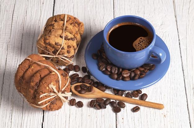 Tazza di caffè e biscotti al cioccolato sul tavolo Foto Premium