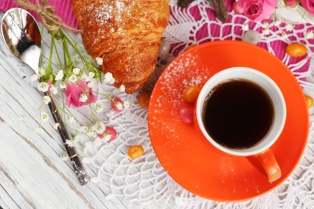 Tazza di caffè e croissant sono decorati dalla piccola torre eiffel, tovaglioli, rose e caramelle su un tavolo di legno bianco Foto Premium