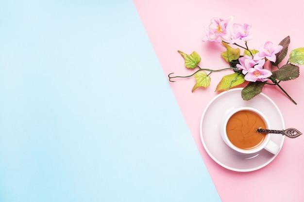 Una tazza di caffè con latte e ramo con fiori e foglie su uno sfondo pastello rosa con spazio di copia. disteso. Foto Premium