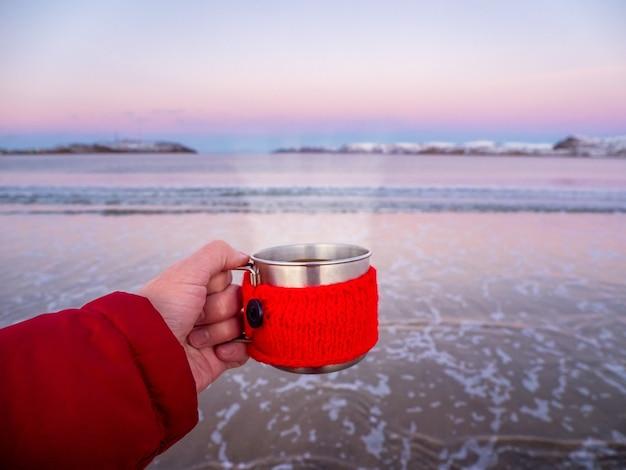 Una tazza di tè caldo con il vapore in mano sulla costa artica Foto Premium