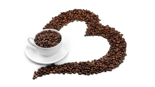 Una tazza con chicchi di caffè nel cuore di chicchi di caffè. molti chicchi di caffè. Foto Premium