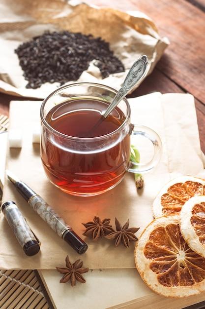 Tazza con tè, foglie di tè essiccate su carta kraft, zuccheri di zucchero, spezie, busta e maniglia su un tavolo di legno Foto Premium