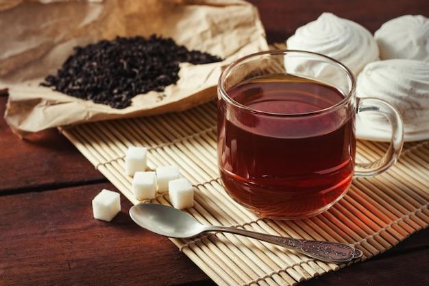 Tazza di tè, foglie di tè essiccate su carta kraft, zuccheri di zucchero e cucchiaio su un tavolo di legno Foto Premium