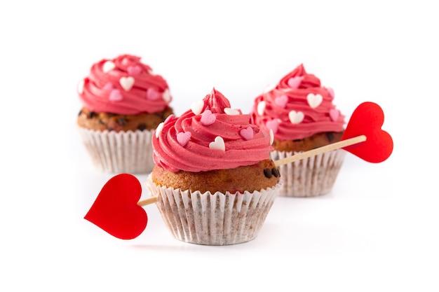 Cupcake decorato con cuori di zucchero e una freccia di cupido per san valentino isolato su priorità bassa bianca Foto Premium