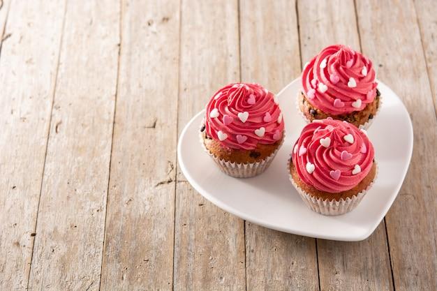 Cupcakes decorati con cuori di zucchero per san valentino sulla tavola di legno Foto Premium