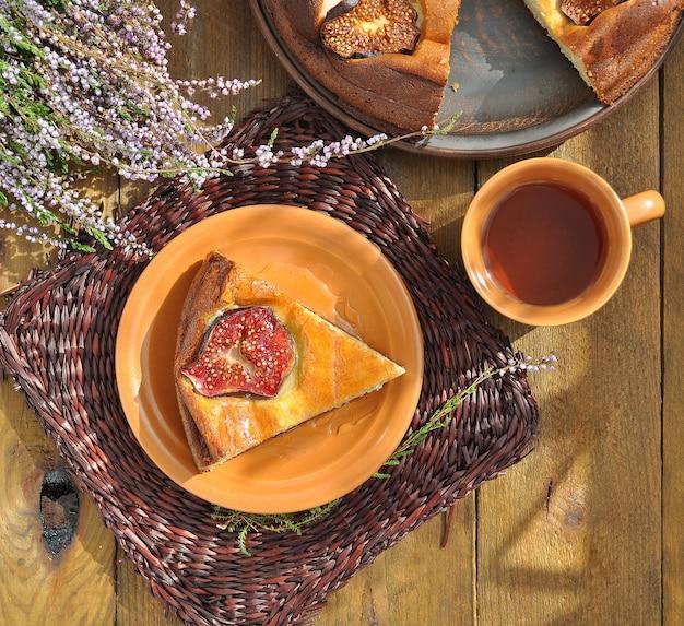 Budino di cagliata con fichi e miele sul tovagliolo marrone di vimini e tisana con erica sui precedenti di legno Foto Premium