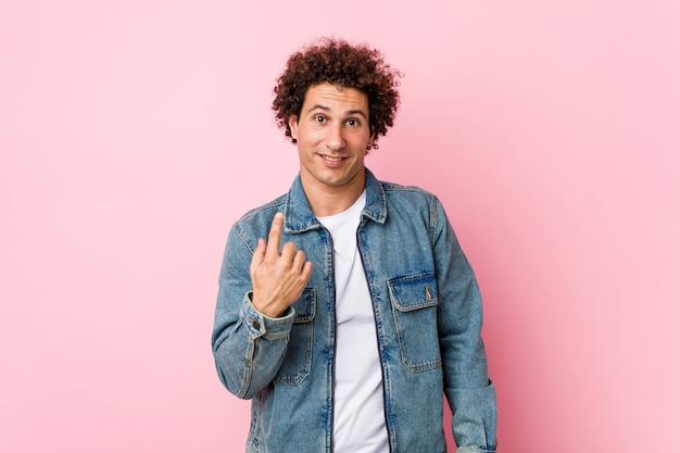 Uomo maturo riccio che indossa una giacca di jeans su sfondo rosa che punta il dito contro di te come se invitando ad avvicinarsi. Foto Premium