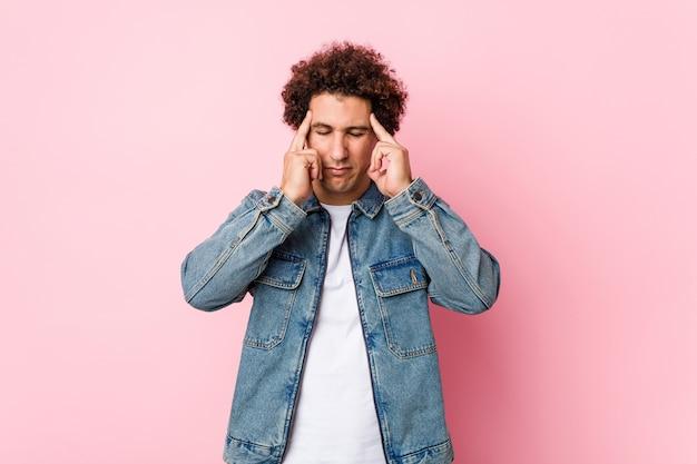 Uomo maturo riccio che indossa una giacca di jeans su sfondo rosa, toccando le tempie e avendo mal di testa. Foto Premium
