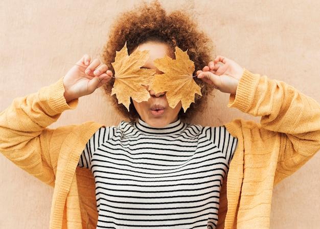 Donna riccia che copre gli occhi con foglie Foto Premium