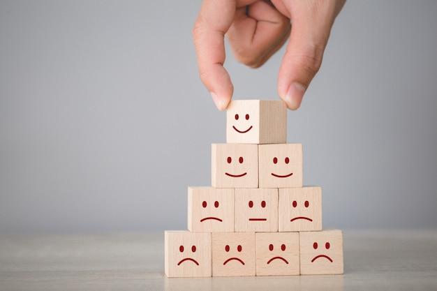 Emoticon del fronte di smiley che preme cliente sul cubo di legno, valutazione di servizio, concetto di soddisfazione. Foto Premium