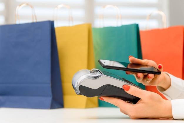 Cliente che utilizza il telefono per il pagamento al proprietario in negozio, ristorante, tecnologia senza contanti e concetto di pagamento con carta di credito Foto Premium