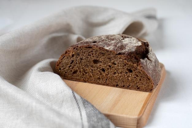 Tagliare il pane di segale nero su una tavola di legno Foto Premium