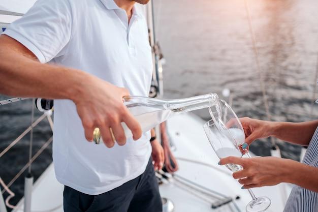 Tagli la vista dell'uomo che versa il champaigne in vetri. la donna li tiene. stanno a prua dello yacht bianco. guy indossa camicia bianca e pantaloncini scuri. Foto Premium