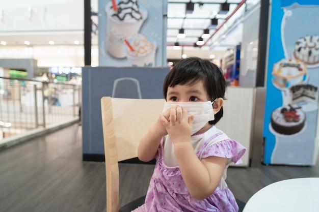 Mascherina chirurgica d'uso del bambino asiatico sveglio e che si siede sul gelato in attesa della sedia nel ristorante Foto Premium