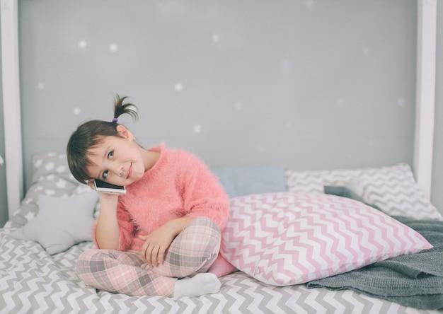 Bambina carina che gioca con uno smartphone, lo smartphone ha un impatto negativo sullo sviluppo e sulla salute mentale di tuo figlio Foto Premium
