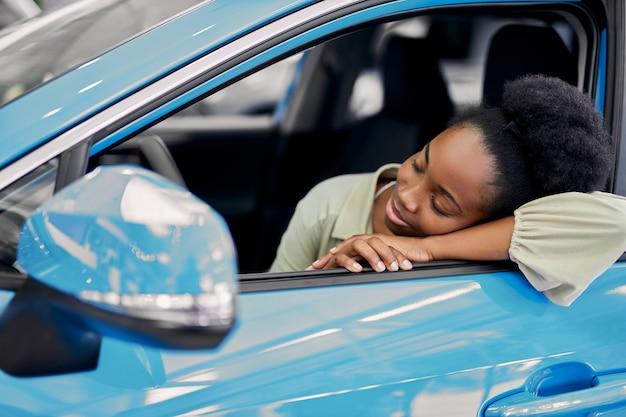 La bella donna sveglia si è appoggiata all'automobile Foto Premium
