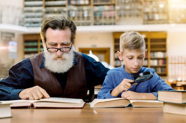 Ragazzo sveglio che tiene il libro di lettura della lente d'ingrandimento con suo nonno bello, seduto al tavolo nella vecchia biblioteca elegante, sullo sfondo di scaffali di libri d'epoca. concetto di giornata mondiale del libro Foto Premium