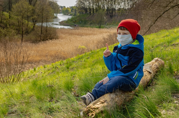 Il ragazzo sveglio in una mascherina medica si siede su una collina su un ceppo e guarda il lago. la famiglia cammina all'aperto con bambini all'inizio della primavera durante la quarantena Foto Premium