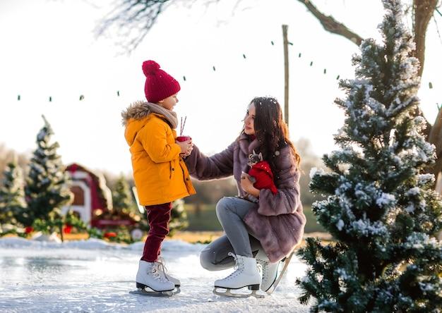 Ragazzo carino con sua madre sulla pista di pattinaggio Foto Premium