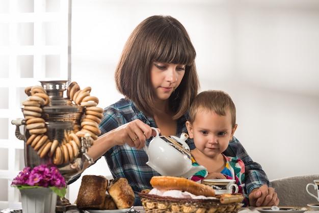Carino madre premurosa versa il tè al piccolo figlio carino Foto Premium