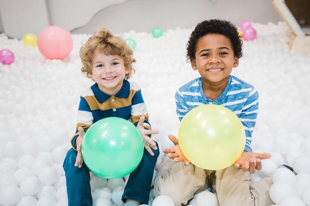 Ragazzini interculturali allegri svegli in camicie a righe che giocano con palloncini verdi e gialli nella stanza dei bambini o all'asilo Foto Premium