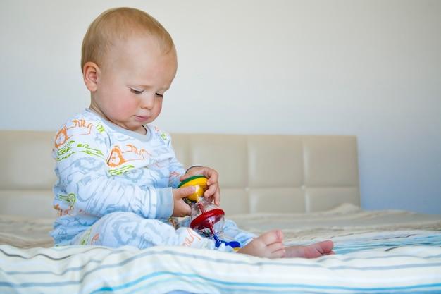 Ragazzo sveglio del bambino che si siede in pigiama sul letto e gioca con il giocattolo colorato. Foto Premium