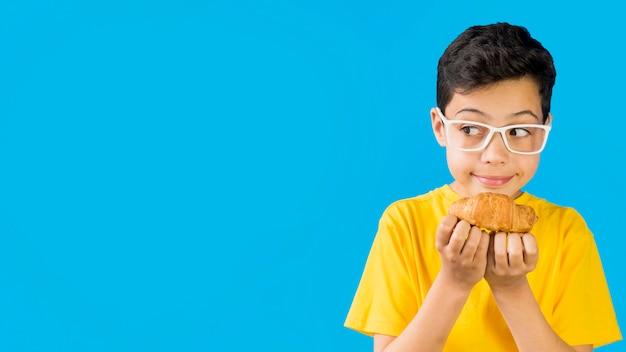 Bambino sveglio che tiene uno spazio della copia del croissant Foto Premium