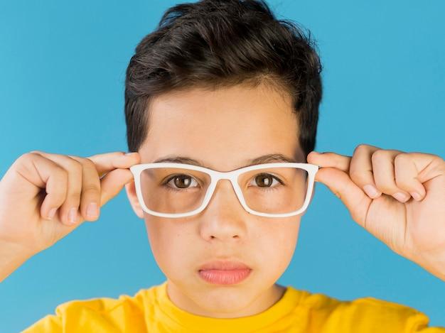 Bambino sveglio che indossa il ritratto di occhiali falsi Foto Premium