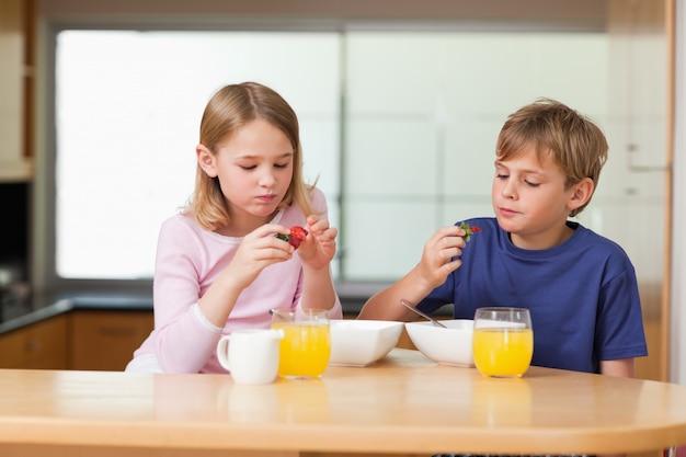 Bambini svegli che mangiano le fragole per la prima colazione Foto Premium