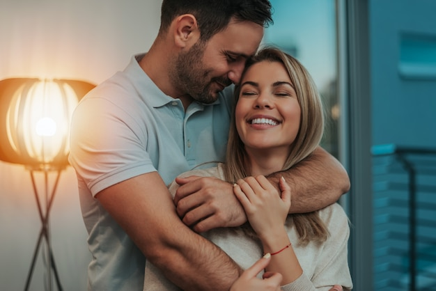 Coppia carina abbracciare e sorridente nella loro nuova casa. Foto Premium