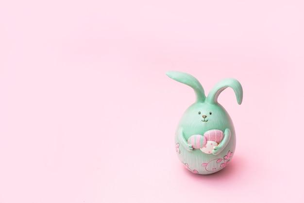 Coniglietto di pasqua creativo sveglio della foto che tiene le uova su fondo rosa con lo spazio della copia Foto Premium