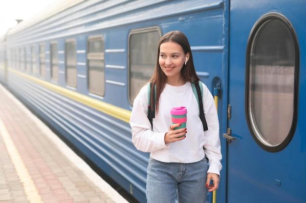 Ragazza carina alla stazione ferroviaria tenendo il caffè Foto Premium
