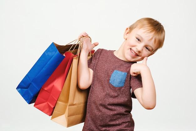 Carino bambino felice con colorate shopping bag Foto Premium