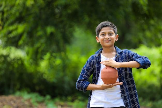 Carino bambino indiano tenendo in mano argilla salvadanaio Foto Premium