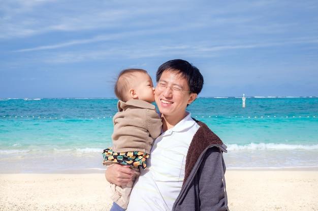 Carino piccolo asiatico 1 anno / 18 mesi bambino neonato bambino bacio papà sulla bellissima spiaggia di sabbia bianca Foto Premium