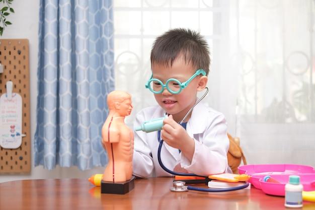 Carino piccolo ragazzo asiatico di 4 anni scuola in uniforme del medico che gioca al dottore a casa, bambino che indossa lo stetoscopio che impara e gioca con il modello di organi del corpo anatomico Foto Premium
